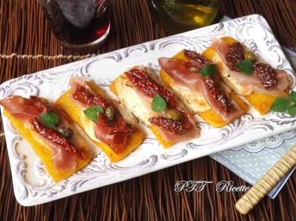 Crostini di polenta con speck, scamorza e pomodori secchi